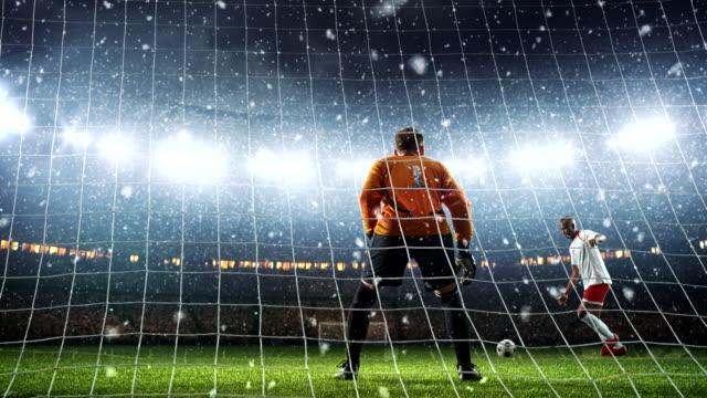 torwart zeigt große speichern aus einem elfmeter, einen ball in einen sprung auf eine professionelle fußball-stadion zu fangen, während es schneit - strafstoß oder strafwurf stock-videos und b-roll-filmmaterial