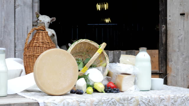 Goat Dairy Farm Products Outdoors on Table With Goats in Stable video
