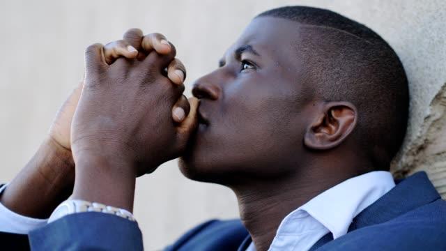 vídeos de stock e filmes b-roll de god,prayer,hope.desperate young black business man praying god - afro