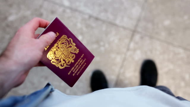 Going on Vacation Point of view shot looking down on someone holding a British passport in their hand while pacing around an airport gate. passport stock videos & royalty-free footage