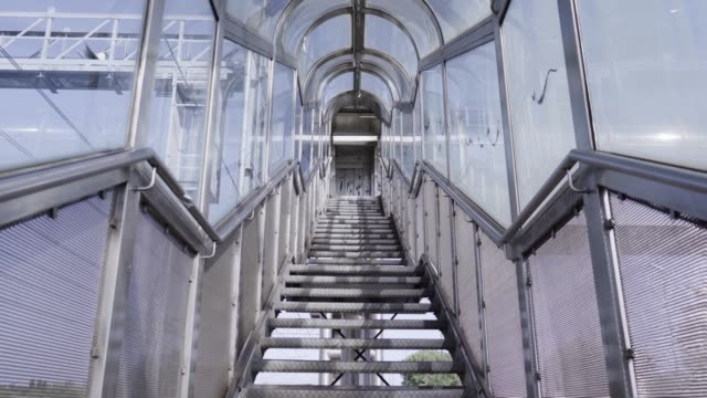 going up steps with glass arch ceiling to road crosswalk