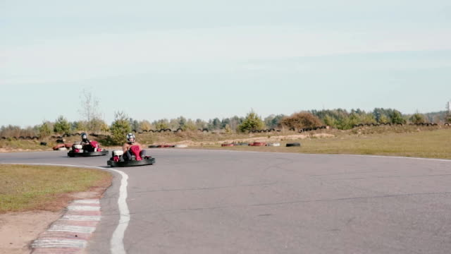 Go-kart track. Two karts moving in the camera and pass by Two karts moving in the camera and pass by. Go-kart track. go cart stock videos & royalty-free footage