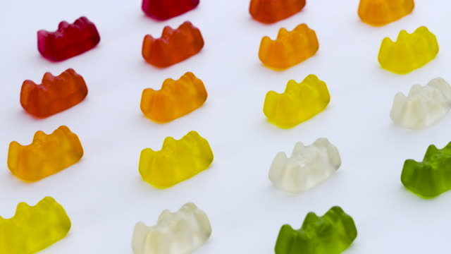 gold bears. colorful animal gummy candies rows are moving diagonally on the white background. - sostanza gelatinosa video stock e b–roll
