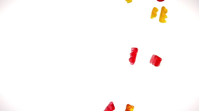 gold bears or gummy bears falling against white background, slow motion - dolci video stock e b–roll