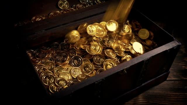 le monete d'oro vengono versate nel vecchio petto di legno - scatola del tesoro video stock e b–roll
