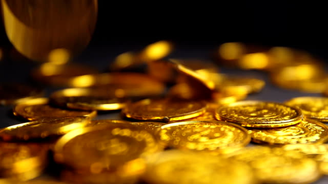Gold coins falling on black background