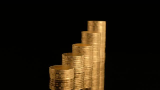 vidéos et rushes de pièces d'or sur pile tournant sur fond noir - abaisser