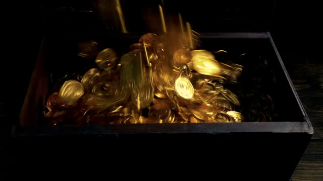 gold coins poured into old wood chest - scatola del tesoro video stock e b–roll
