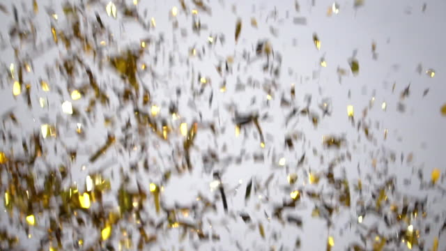 vídeos de stock e filmes b-roll de gold confetti explosion on white background - confetis