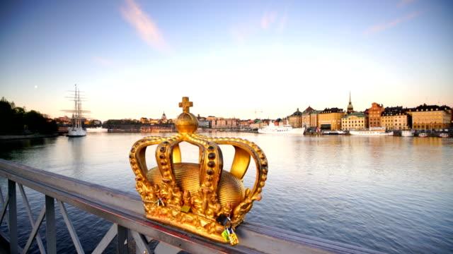 vídeos de stock e filmes b-roll de gold crown on skeppsholmen bridge in stockholm city - coroa