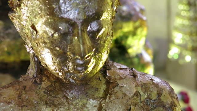 Gold leaf on close-up Buddha video