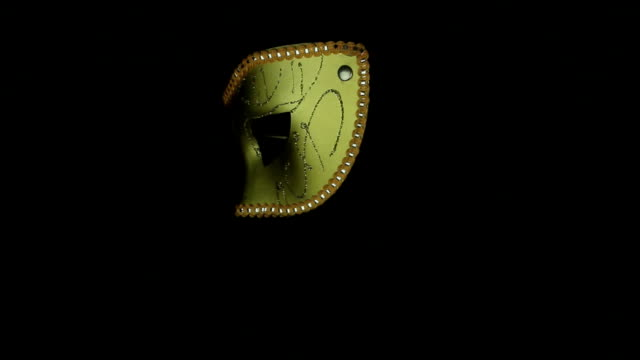 Gold mask rotates on a black background loop video