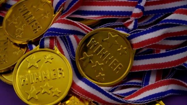 goldmedaillen mit wortsieger und bändern - sportchampion stock-videos und b-roll-filmmaterial