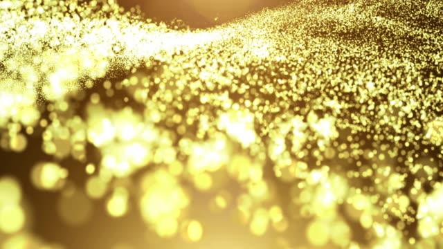 hafif flare ile altın parçacık dalgası - bling bling stok videoları ve detay görüntü çekimi