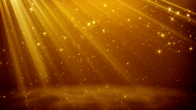 Gold particles and stars flying in light rays loopable background video
