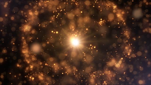 vídeos de stock, filmes e b-roll de partículas de ouro com bokeh pulsando e girando - brilhante luminosidade