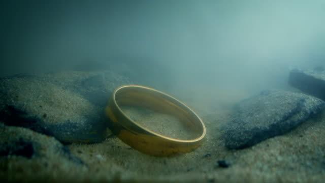 stockvideo's en b-roll-footage met gouden ring druppels op rotsen onderwater - ring juweel