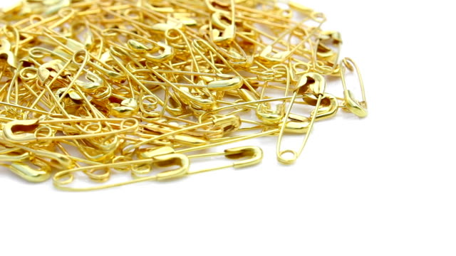 Gold safety pin rotating on isolated