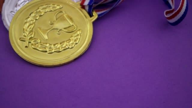 vídeos de stock, filmes e b-roll de medalha de ouro, prata e bronze com fitas em fundo roxo - troféu