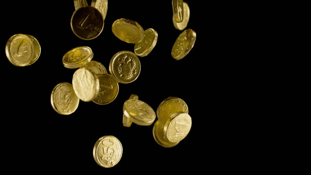 SLO MO LD Gold wrapped chocolate coin falling on black background Slow motion close up locked down shot of gold foil wrapped chocolate euro coins falling down against black background. Shot in Slovenia. coin stock videos & royalty-free footage