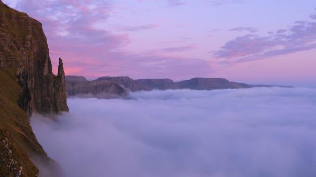 """gyllene höst. rock """"witch ' s finger"""" (trøllkonufingur) vid solnedgången. molnen täckte atlanten. färöarna, europa. - bergsrygg bildbanksvideor och videomaterial från bakom kulisserna"""