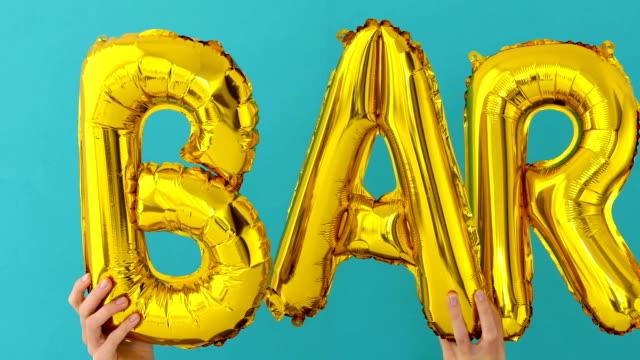 膨脹可能な気球から成っているゴールデンbarの言葉 - バーカウンター点の映像素材/bロール