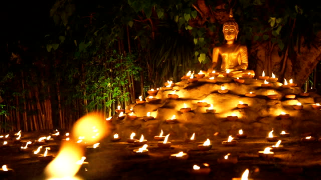 Golden Buddha Statue in sitting pose with candles Golden Buddha Statue in sitting pose with candles at night time buddha stock videos & royalty-free footage
