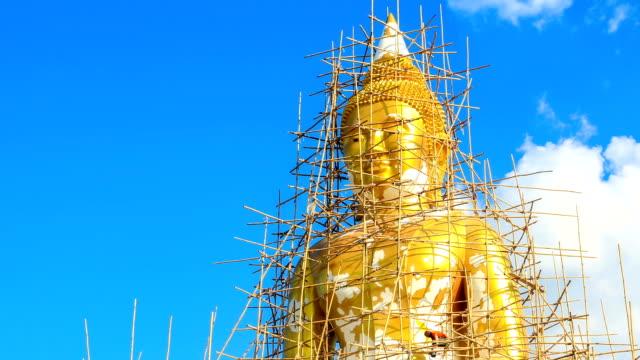 statua dorata del buddha sotto la ricostruzione con cielo blu e nuvole bianche in movimento sfondo con zoom fuori di time lapse - pathum thani video stock e b–roll