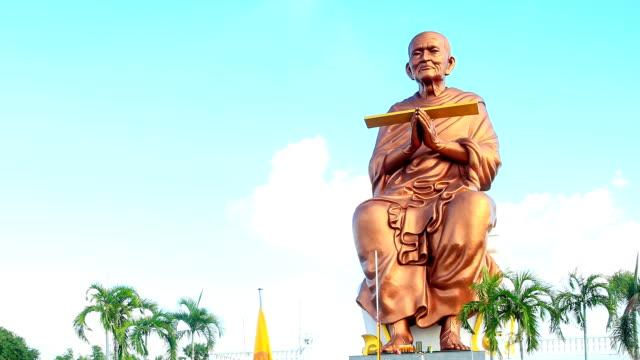 statua di buddha dorato con cielo blu e nuvole in movimento sullo sfondo bianco time lapse - pathum thani video stock e b–roll