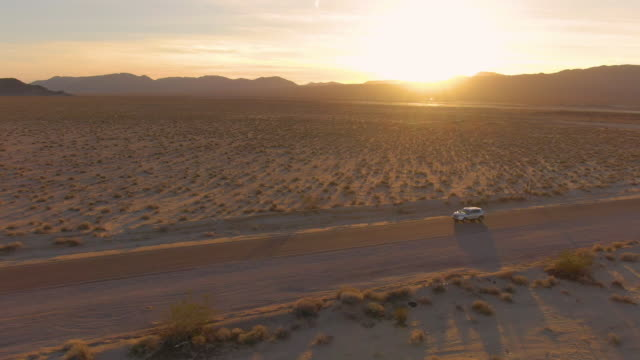 AERIAL: Golden California sunbeams illuminate the landscape for SUV on road trip AERIAL: Golden California sunbeams illuminate the desert landscape for the SUV on a scenic road trip across the Mojave desert. Flying along a car driving down the empty freeway crossing rural Nevada mojave desert stock videos & royalty-free footage