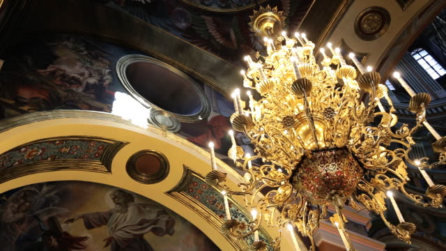 Golden chandelier with imitation candles hang from ceiling of temple Golden chandelier with imitation candles hang from ceiling of temple. Luxurious lighting hangs under painted walls and vault of church. lamp shade stock videos & royalty-free footage