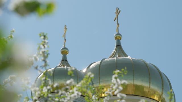 goldene christliche kirche kuppel blühenden apfelbaum klaren himmel sonnigen tag nahaufnahme - religiöses symbol stock-videos und b-roll-filmmaterial