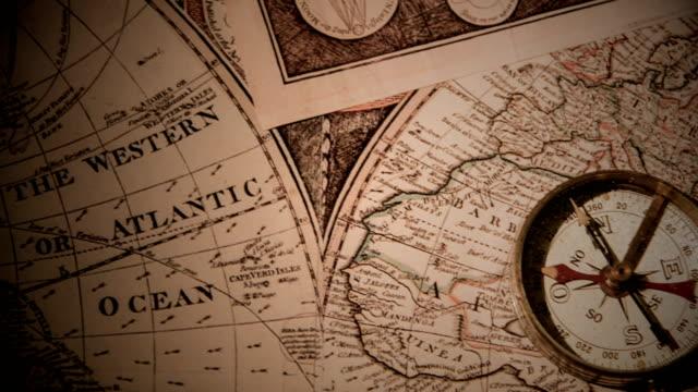 vídeos de stock e filmes b-roll de golden compass on antique map - cartografia
