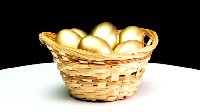 golden eggs in a basket on a black background. golden eggs close-up, easter, spring, investment and retirement concept. camera rotation - cestino video stock e b–roll
