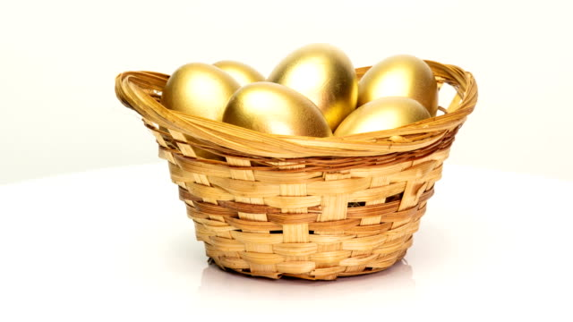 golden eggs in a basket on a white background. golden eggs close-up, easter, spring, investment and retirement concept. camera rotation - cestino video stock e b–roll