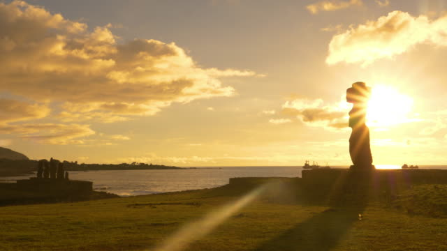 LENS FLARE: Golden evening sunbeams shine on the moai statues by the beach. video