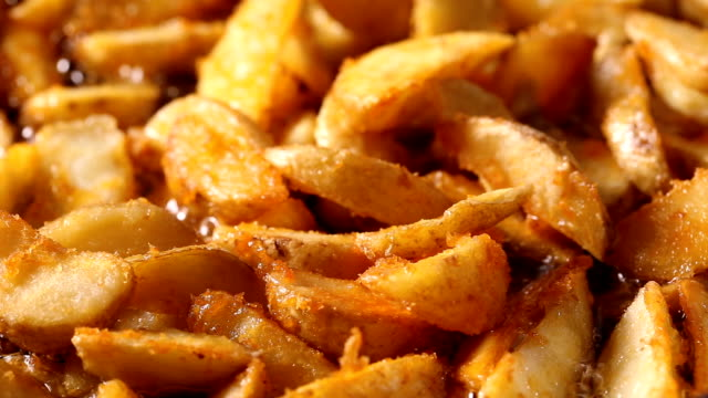 Golden fried potato wedges frying in hot boiling oil Golden fried potato wedges frying in hot boiling oil french fries stock videos & royalty-free footage