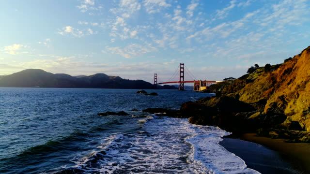 vídeos y material grabado en eventos de stock de vista de drone golden gate puente aérea por encima de las olas en san francisco, california - bahía