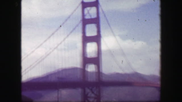 1939: Golden gate bridge pan Fort Point fedora hat man parked classic cars.