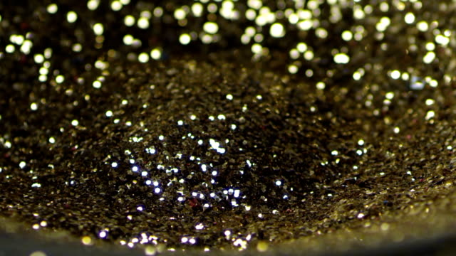Golden glitter dancing, shivering on black loud speaker. Golden glitter exploding , Slow motion video