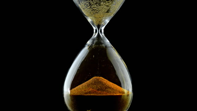 SLO MO LD Golden grains of sand falling through an hourglass video