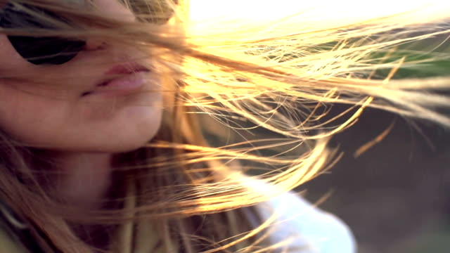 Golden hair and golden sunset Close up of a woman face on a country road during the sunset,while the wind is moving her blonde hair hair stock videos & royalty-free footage