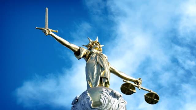 vídeos de stock, filmes e b-roll de estátua de ouro senhora justiça no céu azul - domínio