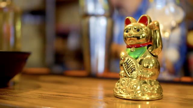 vidéos et rushes de or porte-bonheur maneki neko sur comptoir, restaurant coréen - bonne chance
