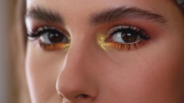 golden makeup for a golden beauty - kosmetyczka praca w salonie piękności filmów i materiałów b-roll