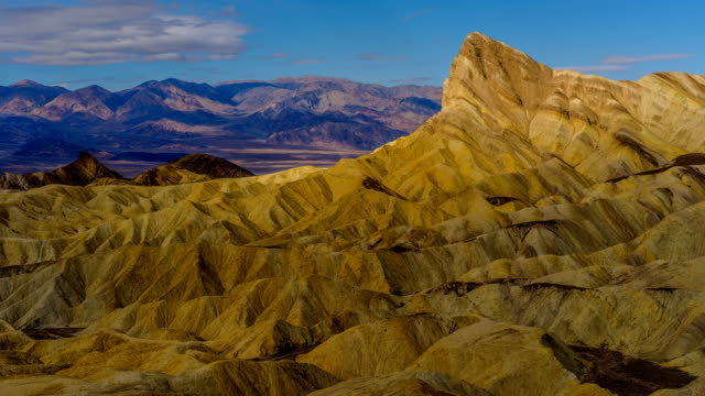 vídeos de stock e filmes b-roll de golden manly beacon - time-lapse video of panoramic morning view of spring clouds passing over manly beacon and surrounding rolling hills, gullies and canyons, with panamint range in background. zabriskie point, death valley national park, ca, usa. - parque nacional do vale da morte