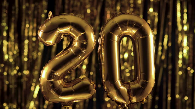 Golden number 20 twenty from an inflatable balloon, on a yellow background. One of the complete set of numbers. The concept of birthday, anniversary, date Golden number 20 twenty from an inflatable balloon, on a yellow background. One of the complete set of numbers. The concept of birthday, anniversary, date anniversary stock videos & royalty-free footage