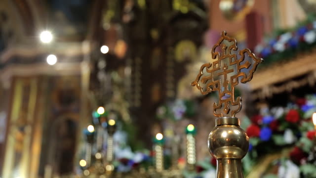Golden orthodox cross on background of rich decoration of church video
