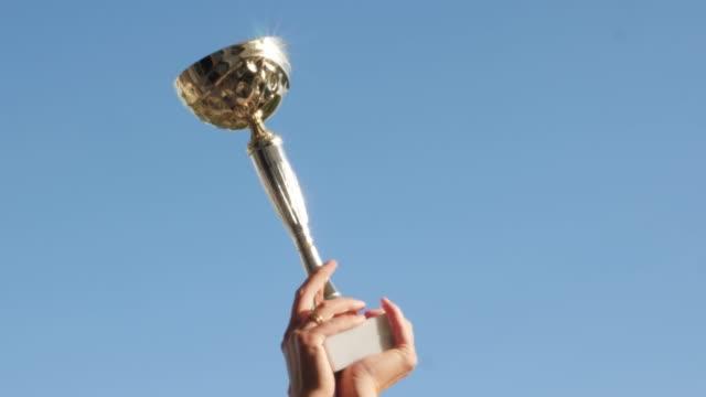 vídeos de stock e filmes b-roll de golden, shiny in the sun the winner's cup against the blue sky - campeão desportivo
