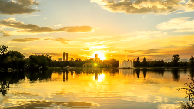 golden sunset at city park - a summer sunset view of ferril lake in denver city park, with city skyline and front range mountains in the background, at east-side of downtown denver, colorado, usa. - колорадо стоковые видео и кадры b-roll
